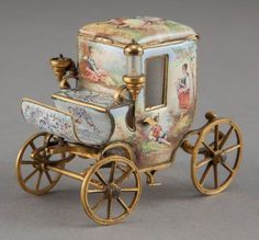 A VIENNESE GILT METAL AND ENAMEL MINIATURE CARRIAGE   Maker unknown, Vienna, Austria, circa 1900  Unmarked  2-3/8 x 2-7/8 x 1-5/8 inches (6.0 x 7.3 x 4.3 cm)    The miniature gilt metal carriage with enamel on copper scenes of couples within a landscape, with hinged top fitted with gilt metal cover.