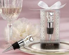 """LOVE"" Wedding Wine Bottle Stopper made of solid chrome with a notable weight and quality. It features a long conical base wrapped with a black rubber gasket for a tight seal. The top of the bottle stopper has the word ""LOVE"" with a heart replacing the ""O"". It comes packaged in a clear gift box with a pink, gray, and white damask design on the base. It is decorated with a white satin ribbon."