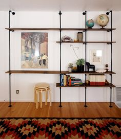 DIY bookshelf pulled together for around $200. This wall-size unit would be impressive no matter what, but when you factor in the do-able budget, accessibility of the materials (basic plumbing pipes/fittings and pine planks) and the sturdiness of the finished piece, it's elevated to a DIY masterpiece.