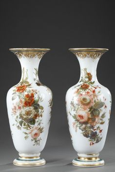 A pair of baluster shape vases in white enamelled opaline, decorated with red, white an blue bunches of flowers. The collar is hightened with gilded arabesques and the base with...