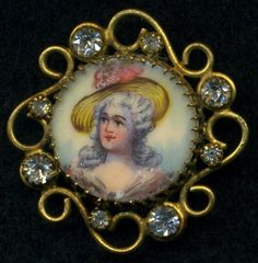 Antique hand painted button with swirly brass border and pastes.