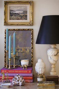 Feminine chic, with a vintage touch. Candlesticks, vintage art/frames, marble lamp-- love seeing these treasures on display. Smart choice using colorful books to brighten the space, and the little brass objects and ceramic sculpture add charming quirkiness to the vignette.