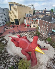 Florentijn Hofman realizes giant climbable party aardvark in Arnhem, the Netherlands. In the back the Rozet building by Neutelings Riedijk Architects.