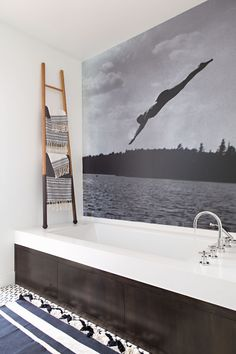In this modern bathroom, the wall above the bath is covered with art, while a ladder provides a place to hang towels. #BathroomDesign #ModernBathroom