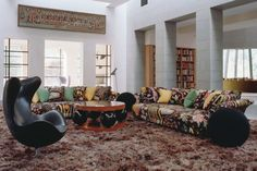 Josef Frank Fifties sofas covered in 'Hawaii' by Svenskt Tenn stand on a shag-pile Mongolian sheepskin rug, alongside a table by Erik Johansson and an Egg chair by Arne Jacobsen. The Great Hall, Corrour Lodge, Scottish Highlands, designed by architect Moshe Safdie.