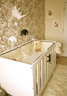 Lovely gold and white nursery. I'd probably move that extra pointy rhino off to the side and not directly over the crib though :)