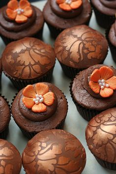 Autumn Cupcakes...Chocolate cakes, with chocolate buttercream topped with orange flowers or embossed and gilded belgian chocolate...no recipe...just a gorgeous photo on flickr http://www.flickr.com/photos/13041737@N08/with/5105086752/