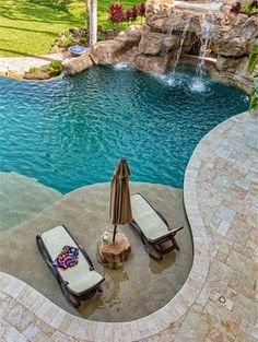 Custom swimming pool in River Oaks Estate with tanning ledge, stone rock grotto and travertine deck