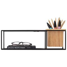 A hip wire shelf display with a multifunctional cup and a removable shelf to accommodate different orientations. Can hold books, frames or a combination of different personal items. Wooden shelf can become a tumbler for small pieces or a pot for small plants (with plastic insert). Designed by Erika Kovesdi, this innovative shelf can alternately sit on the desk or be hung on the wall. Holds 15 lbs max. Mounting hardware included.