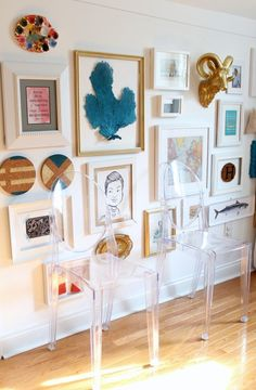 This is such a fun, eclectic gallery wall. Tones of gold, blue and white are prominent. And, you almost don't even notice the ghost chairs sitting right in front of it! These chairs are a brilliant way to add seating without getting in the way of your fantastic art collection!! Let your art dictate the design of a space and see what happens... We think you'll be pleasantly surprised.