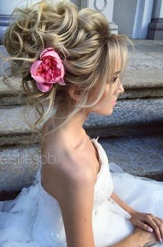 This loose wavy updo wedding hairstyle is simply gorgeous with a pink flower hairpiece