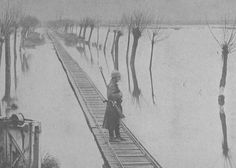 Belgian soldier guarding railroad constructed over flooded lowlands, 1917.