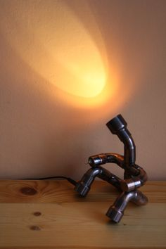 Cute light man. The lamp was made by antiqued copper fittings. It operates from 12 V and 2 W LED bulb is into head. The brightness is low, therefore I recommend for mood lamp. You can light the lamp exc wall, picture, or little statue. The head is rotating. The switch is in hand, the jack is in leg. Does not heat up, and not consume much. Mood Lamps, Can Lights, Unique Lamps, Secret Life, Antique Copper, Table Lamp, Bulb, Statue, Led