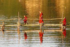 Buddhist monks on a footbridge, Irrawaddy River Myanmar