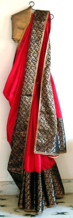 Look stunning in this bright red saree with wide black brocade border and bronze trims. The saree comes with 1 meter matching blouse fabric in