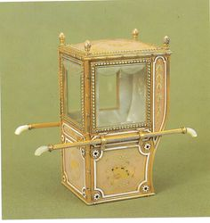 The enameled miniature sedan chair recalls Louis XVI design. The translucent pink is painted over starburst guilloche ground with gold leaf within opaque white enamel borders. This is one of the most impressive examples of the enamel technique.