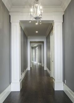 Lane Myers Construction Custom Home Builder Loeffler Residence Draper Utah Versailles Inspired Hallway Hardwood Floors Dark Gray Walls White Trim