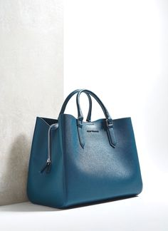 0458b98911 Vegan leather tote bag featuring three distinct compartments. The middle  section fastens with a zipper