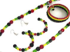 This #JewelrySet comes with hoop earrings, a stackable bracelet, and necklace. All pieces are designed with black, green, yellow, and red glass beads. #taraelisabethdesigns #Handmade #HandmadeJewelry #Jewelry #FashionJewelry