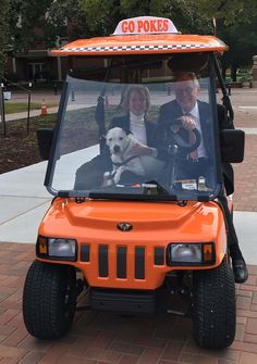 Pete's Pet Posse therapy dog, Scruff, rides around the campus in Clementine with OSU President Burns Hargis and First Cowgirl Ann Hargis.