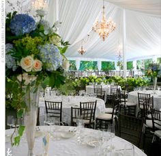 """""""Centerpieces in varying heights topped the guest tables. The arrangements of roses, hydrangeas, and other blooms spilled from the tops of silver vases."""" I love the outdoor reception under a covered tent."""