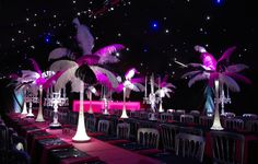 Illuminated feather table centres and glass candelabra in a marquee for a Rio Carnival themed corporate event or private party from www.stressfreehire.com #venuetransformers