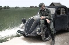 German soldier taking a break, while sitting on Fiat Simca Topolino.