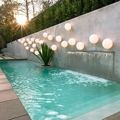 narrow pool with backdrop wall water feature, accent planter and decorative lighting element orbs on the wall.