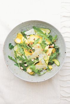 Shaved Zucchini Salad with Almonds & Asiago | 1/4 cup (2 fl oz/60 ml) extra-virgin olive oil, 2 Tbs. fresh lemon juice,, 1 clove garlic, pressed, Kosher salt and freshly ground pepper, 3/4 lb (375 g zucchini, trimmed, 1/4 cup (1/3 oz/10 g) chopped fresh flat-leaf parsley leaves, 1 cup (1 oz/30 g) baby arugula leaves, 1 oz (30 g) Asiago cheese, shaved, 2 Tbs. almonds, toasted and chopped