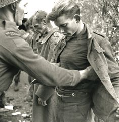 A Canadian Soldier searches a young German P.O.W