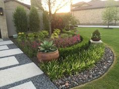 Stone EDGING Haven -- This garden edging idea is perfect for creating a symmetrical garden that looks the same on both sides of the walkway to the door. The garden is full of potted plants, and perfectly trimmed plants that are growing in the ground. The border between the garden and the grass is designed using a plethora of medium-sized rocks.