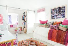 Colorful textiles in all-white children's room