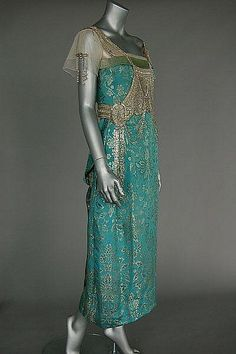 A turquoise and gold brocaded satin evening gown, circa 1917, un-labelled, the bodice adorned with tasselled panel of silver bugle beads, tulle sleeves, above draped skirt with wide inner petersham waistband. Sideway