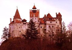 "Bran Castle in Transylvania, Romania. Although this Century fortress is one of several castles linked to the Dracula legend, Bran Castle deviously snatched the nickname of ""Dracula's Castle"" and all the marketing rewards that flowed. Draculas Castle Romania, Count Dracula Castle, Real Castles, Vlad The Impaler, Castle Pictures, Carpathian Mountains, Castle In The Sky, Haunted Places, Scary Places"
