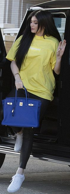 Who made  Kylie Jenner's yellow tee, black leather leggings, white sneakers, and blue tote handbag?