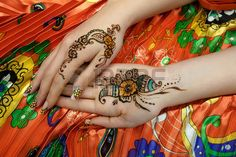 Indian picture on hands palms, mehendi tradition decoration, resistant design by special paint, brown, orange green henna. Long colorful nails new shape manicure nail extension. Saloon service style
