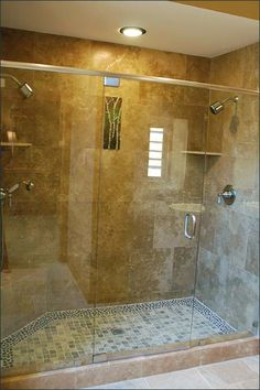 Master bathroom walk in invisable glass and travertine shower with pebble stone floors and artisan tile..