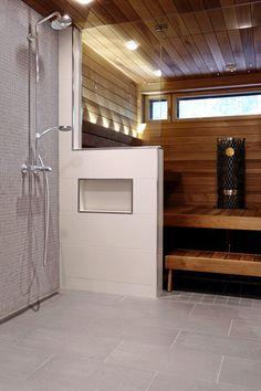 Saunatilan harmaat laatat, syvennys pesuaineille, lasiseinä. ABL-saunatilat laatat harmaa mosaiikki kylpyhuone suihkuseinä