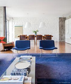 Sala de estar tem cadeiras e tapete na cor azul. Ao fundo vemos poltrona assinada por Carlos Motta.