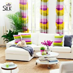 Compliment your white sofa with matching colorful drapes & cushions.