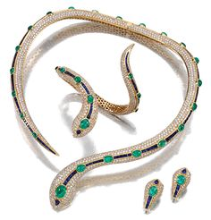 EMERALD, SAPPHIRE AND DIAMOND PARURE.  Comprising: a hinged necklace designed as a snake, the body set throughout with brilliant-cut diamonds and decorated with a line of calibrated sapphires and cabochon emeralds, accompanied by a pair of earrings and a bangle en suite, all mounted in yellow gold,  necklace circumference approximately 390mm, bangle circumference approximately 150mm.