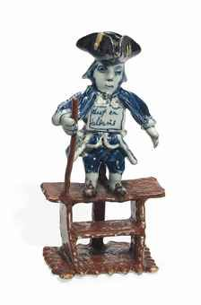 A DUTCH DELFT POLYCHROME FIGURE OF A 'THIEF AND A LIAR' LATE 18TH CENTURY The prisoner modelled standing chained to a pole on a two-stepped brown platform, supporting himself with a staff in his right hand, wearing a manganese tricorn hat, blue and white jacket and waistcoat, blue breeches and manganese shoes, with a notice hung around his neck inscribed dief en soldaris