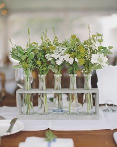 The long farm tables were dressed with linen runners. Centerpieces of wooden bases held glass test tubes of petite white flowers and assorted greenery.