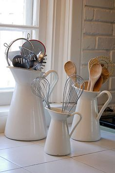 Pitchers. Cute way to organize your kitchen utensils. Then if you need a pitcher, just take the utensils out and there ya go!