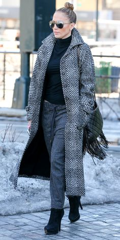 J.Lo kept warm in a gray look that she anchored with a chic houndstooth duster coat. Skyhigh platform booties and a quilted fringe shoulder bag accented her winter ensemble.