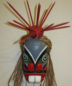 The #Pugwis is the man of the sea; he serves as the messenger for #Kumugwe. He is often portrayed with a sea bird or sea life on the top of his head. On this mask he has the sea urchin.  This #mask was carved out of red cedar wood and has yellow cedar bark around the head, created by Willie Hawkins. #Northwestcoast #FirstNations #AboriginalBC