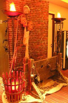 London Clubs International - Halloween set piece including fake dungeon wall, fake brazier, silk flambeaux, stocks plus severed heads on sticks by www.stressfreehire.com #venuetransformers