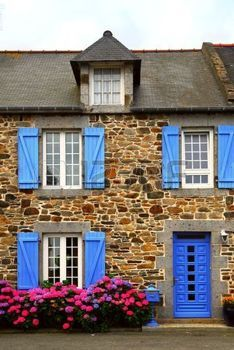 Typical country house with blue shutters in Brittany, France