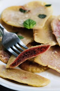 Vegan Red Beet Pesto Ravioli by Pasta-based. Close-up of a ravioli cut open and creamy red beet pesto in the middle.
