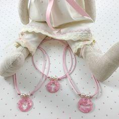 Pequeñas gargantillas para niñas que les gusta ser coquetas. Se trata de medallones de 2,5cms redondas, en los que tienen troqueladas diferentes motivos. Medallón en rosa nacarado montado en cordón de algodón corredero y con dos perlitas de resina a ambos lados.